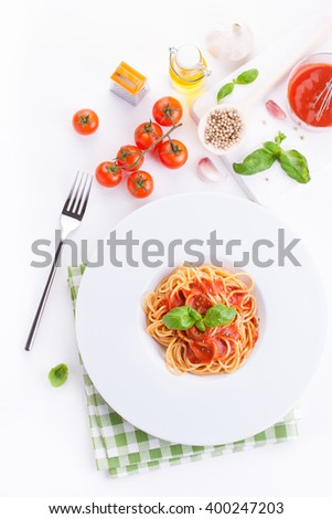 Tomato pasta spaghetti with fresh tomatoes, basil, italian herbs and olive oil in a white bowl on a white wooden background, top view