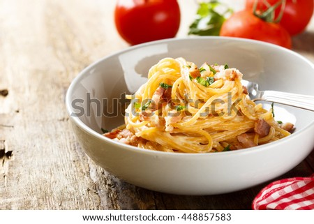 Tomato pasta with egg sauce, cheese and ham - stock photo