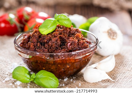 Tomato Pesto (with Parmesan Cheese and Garlic) on wooden background - stock photo