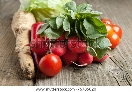 Tomato, radishes and green salad on old wooden table - stock photo