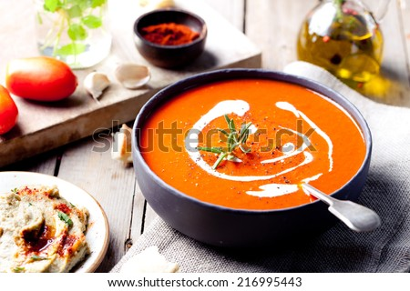Tomato, red pepper soup, sauce with olive oil, rosemary and smoked paprika on a wooden background. Copy space. - stock photo