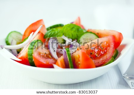 Tomato salad with cucumber and onion - stock photo