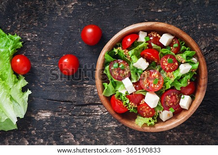 Tomato salad with lettuce, cheese and mustard and garlic dressing. Top view - stock photo