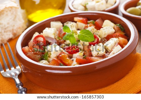 tomato salad with marinated feta cheese and herbs - stock photo