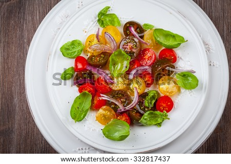 Tomato salad with onions and basil - stock photo