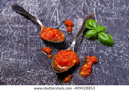 Tomato sauce in the spoon on a dark surface. Selective focus. - stock photo
