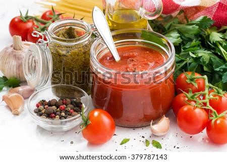 tomato sauce, pesto and ingredients for pasta on a white table, closeup, horizontal - stock photo