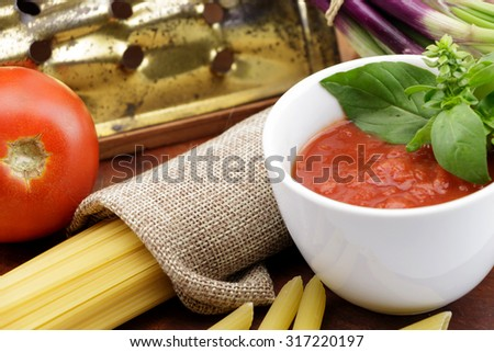 Tomato sauce with fresh basil leaves and tomatoes - stock photo