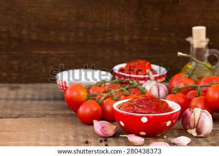 tomato sauce with ingredients on a rustic table - stock photo