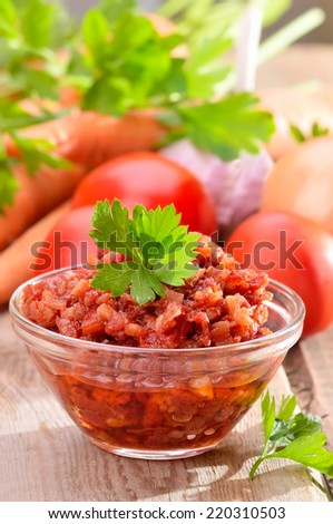 Tomato sauce with pepper, onion and parsley in glass bowl on rustic wooden table - stock photo