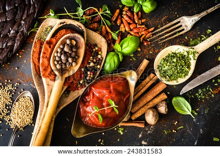 tomato sauce with spices and textured black kitchen table - stock photo