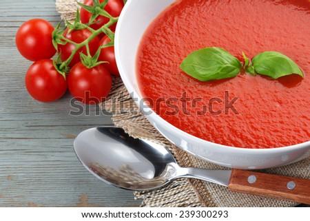 tomato soup, cherry tomatoes, napkin and spoon - stock photo