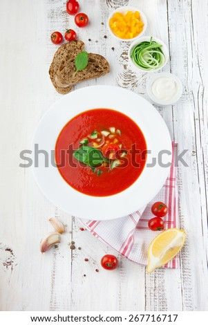 Tomato soup gazpacho and ingredients on white wooden background, top view - stock photo