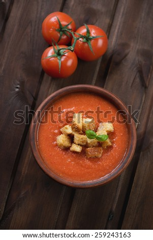 Tomato soup Gazpacho over dark wooden surface, high angle view - stock photo