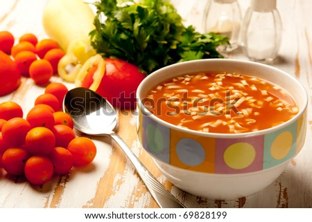 Tomato soup in a bowl with fresh ingredients and herbs - stock photo