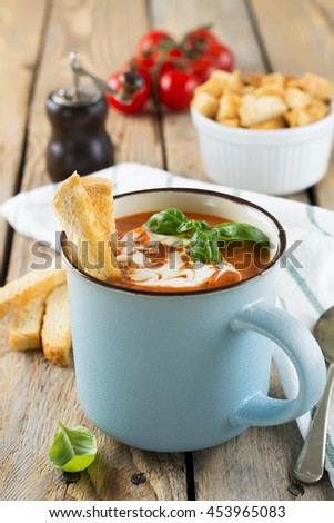 Tomato soup in a ceramic cup on the old wooden background. Selective focus. - stock photo