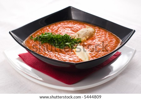 Tomato soup in black plate - stock photo