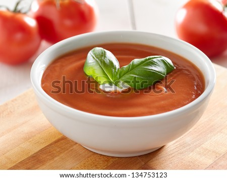 tomato soup with basil garnish. - stock photo