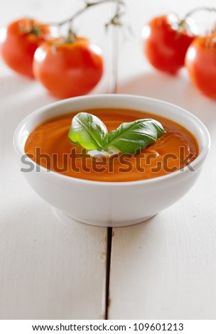 tomato soup with basil garnish and copyspace composition - stock photo