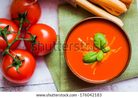 Tomato soup with bread sticks and basil on wooden background - stock photo