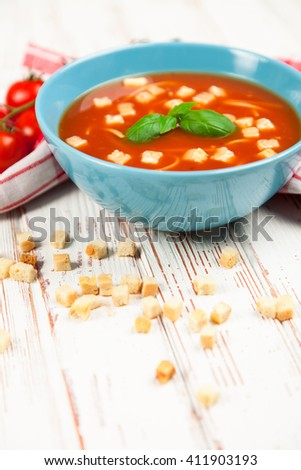Tomato soup with croutons and basil on wooden table - stock photo
