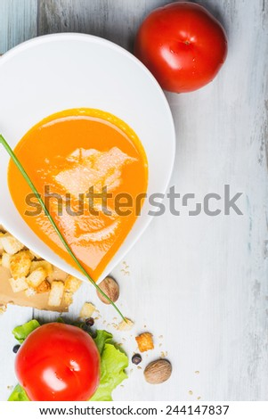 Tomato soup with croutons and shredded cheese on the decorated wooden table  - stock photo