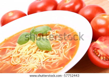 Tomato soup with macaroni decorated with basil with fresh tomatoes around it - stock photo