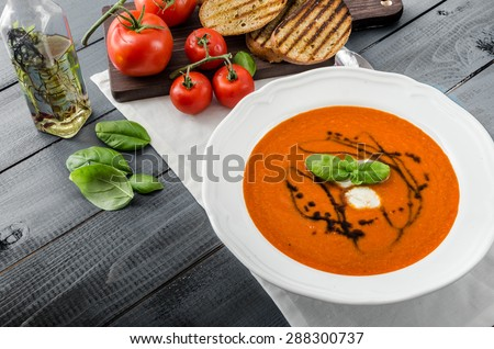 Tomato soup with mozzarella, balsamic winegrad and basil, bruschetta toasts - stock photo