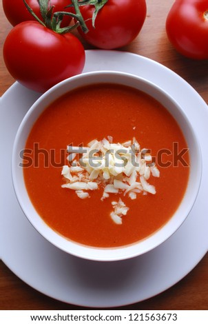 Tomato soup with shredded cheese in ceramic bowl - stock photo