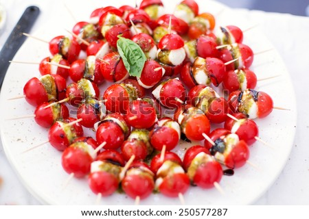 Tomato with cheese on toothpick - stock photo