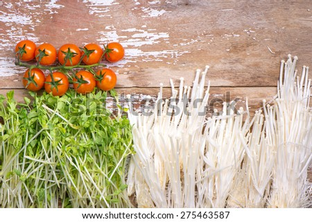 Tomato with Pea Sprout and Golden needle mushroom on wood top. - stock photo