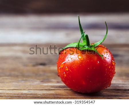 Tomatoe on old wooden table. - stock photo