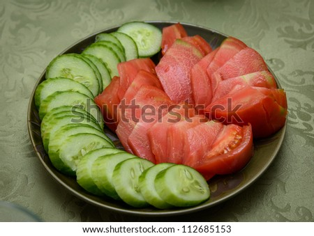 Tomatoes and cucumbers on the plate - stock photo