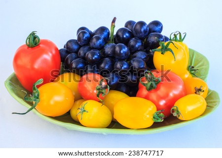 Tomatoes and grapes on a plate - stock photo