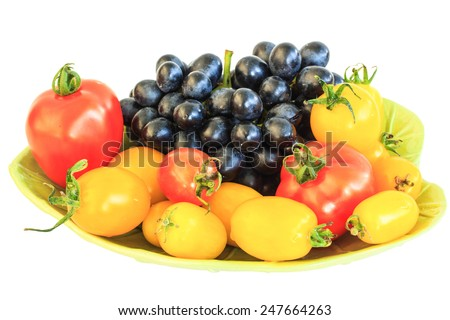 Tomatoes and grapes on a plate isolate on white background. - stock photo
