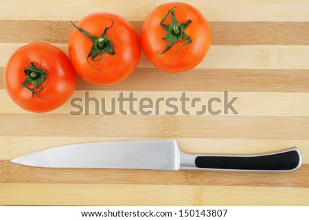 Tomatoes and knife on wooden background  - stock photo
