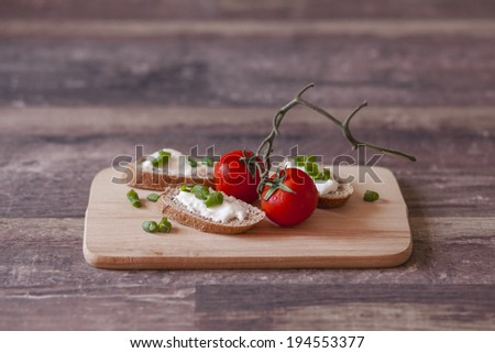Tomatoes and slices of bread with cheese and green onion - stock photo