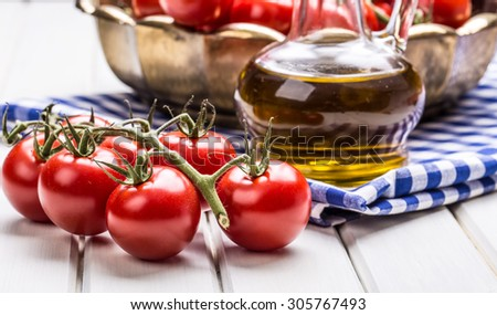 Tomatoes. Cherry tomatoes. Cocktail tomatoes. Fresh grape tomatoes carafe with olive oil on table. - stock photo