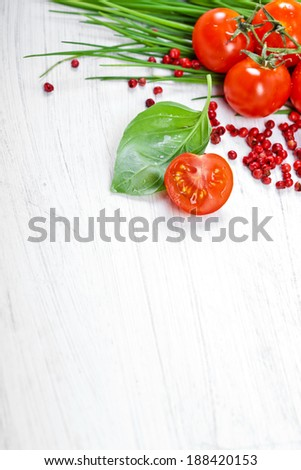 Tomatoes, chives, peppers, herbs on white - stock photo