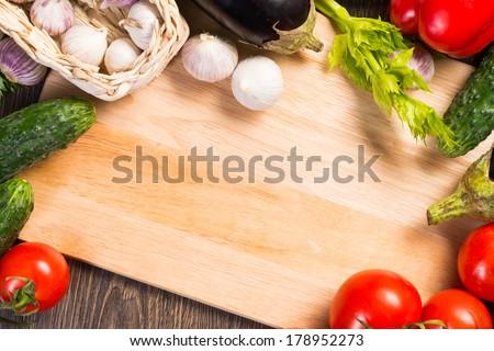 tomatoes, cucumber, garlic, fresh herbs on chopping board - stock photo
