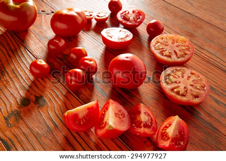 Tomatoes in a red monochrome rustic wooden table - stock photo