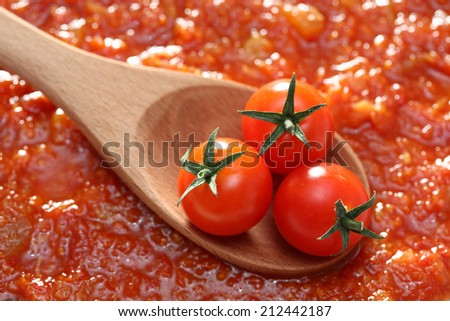 Tomatoes in a wooden spoon on tomato sauce background. Close-up. - stock photo