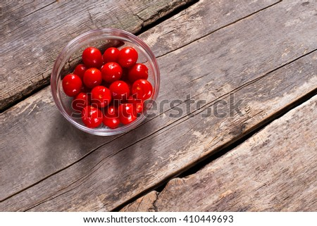 Tomatoes in glass bowl. Tomatoes on brown wooden backround. Fresh juicy vegetables. Ingredient for a salad. - stock photo
