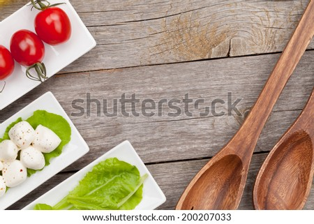 Tomatoes, mozzarella and green salad leaves on wooden table background with copy space - stock photo