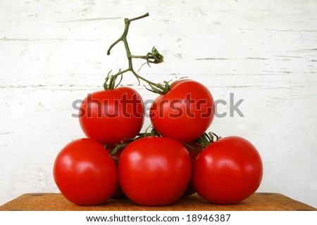 Tomatoes on the vine, stacked in a pyramid shape against a weathered white background - stock photo