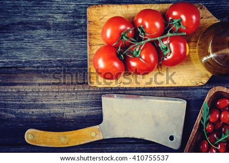 Tomatoes on vine, cherry tomatoes, arugula, olive oil and old butcher cleaver on wooden table. Italian cooking food background - stock photo