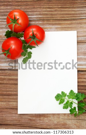 Tomatoes on wood with white notepad - stock photo