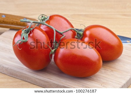 tomatoes on wooden board - stock photo