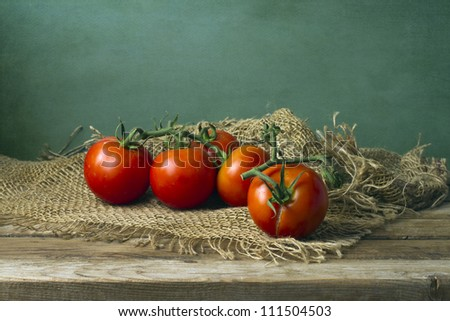 Tomatoes on wooden table and mesh cloth - stock photo