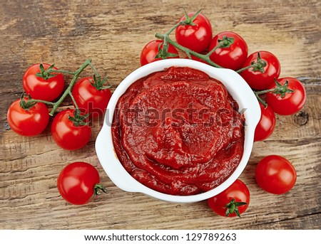 tomatoes paste with ripe tomatoes on wooden tables - stock photo